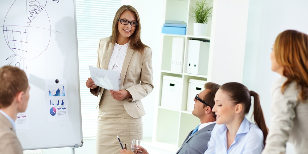 Confident top manager standing by the whiteboard and making report at meeting